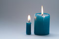 Pair colorful greenish-blue, turquoise candles on gradient gray background. Two pieces. each candle with natural flame