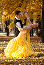Pair of dancers dancing in the woods. Man with suit, woman in yellow long dress  middle of the palace park in autumn. Dry fallen c Royalty Free Stock Photo