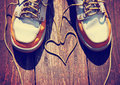 A pair of deck shoes on a nice wooden porch with the laces in shape heart Stock Images