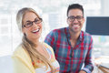 Pair of designers sit in their office smiling Royalty Free Stock Photo
