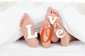 Pair of feet under duvet with love text in white and red Stock Photos