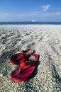Pair of flip flops on a beach pebbly with umbrella in background Royalty Free Stock Image