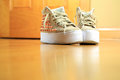 Pair of funky used sneakers shoes on hard wood floor Royalty Free Stock Photo