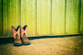 Pair of girls cowboy boots against a green barn. Royalty Free Stock Photo