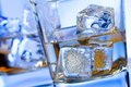A pair of glasses of alcoholic drink with ice on disco blue light Royalty Free Stock Photo