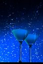A pair of glasses of blue cocktail on table dark tint light bokeh background Royalty Free Stock Photos