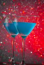 A pair of glasses of blue cocktail on table red tint light bokeh background Royalty Free Stock Images