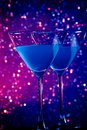 A pair of glasses of blue cocktail on table and violet tint light bokeh background Royalty Free Stock Photos