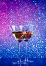 A pair of glasses of cocktail on bar table blue and violet tint light bokeh background Royalty Free Stock Image