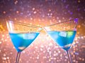 A pair of glasses of fresh blue cocktail with ice make cheers on colorful tint light bokeh space for text Stock Photos