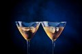 A pair of glasses of fresh cocktail with ice on bar table blue tint light background Stock Images