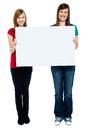 Pair of good looking women holding whiteboard Royalty Free Stock Photos