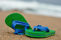 A pair of green and blue flip flops on the beach Royalty Free Stock Photo
