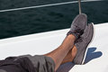 A pair of hairy man legs in pants and topsiders on white yacht deck yachting Stock Images