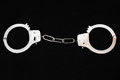 Pair of handcuffs one on a black background Stock Image