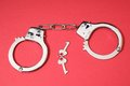 Pair of handcuffs one on a colored background Stock Photos