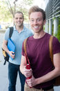 Pair of happy young male students on campus Stock Photos