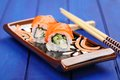Pair of japanese rolls with salmon and cucumber on flat plate wi Royalty Free Stock Photo