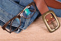 Pair of jeans, glasses and a belt on a table Royalty Free Stock Photo