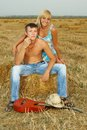 A pair of lovers in the hay with guitar fun on summer at sunset Royalty Free Stock Photography
