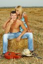 A pair of lovers in the hay with guitar fun on summer at sunset Royalty Free Stock Photo