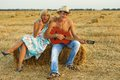 A pair of lovers in the hay with guitar fun on summer at sunset Stock Image