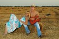 A pair of lovers in the hay with guitar fun on summer at sunset Stock Images