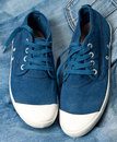 Pair of new blue shoes on a jeans Stock Image