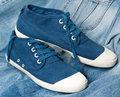 A pair of new blue shoes on jeans Royalty Free Stock Photo