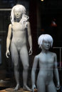 Pair of nude teenaged mannequins closeup two girl boy wearing blond wigs in shop window vintage over blur background black and Stock Image