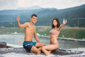 Pair with perfect figure sitting on the Jacuzzi lowered feet in the water and showing thumbs up gesture of good class Royalty Free Stock Photo
