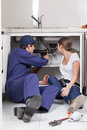 Pair of plumbers fixing the pipe of the kitchen Royalty Free Stock Photo