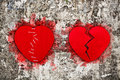 Pair of red broken hearts on aged wall texture Stock Photo