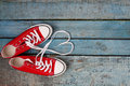 A pair of red retro sneakers on a blue wooden background, laces Royalty Free Stock Photo