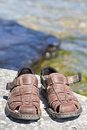 Pair of sandals on rock with water in background Royalty Free Stock Photos