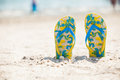 Pair of sandals in sand beach Royalty Free Stock Photo