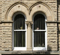 Pair semi circular stone arched windows architecture at saltaire near bradford west yorkshire Stock Photos