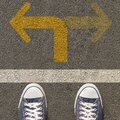 Pair of shoes standing on a road with two way yellow arrow Royalty Free Stock Photo