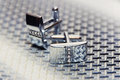 Pair of silver cuff links on the man's tie Royalty Free Stock Photo
