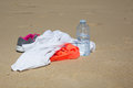 Pair of sports gym shoes on sand with water and shirt