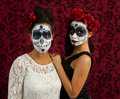 A pair of sugar skull on a red background two beautiful young women with makeup and flowers in their hair stand together against Royalty Free Stock Images