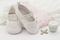 Pair of white baby shoes on embroidered christening white dress, Royalty Free Stock Photo