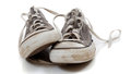 A pair of worn out gray sneakers on a white background Royalty Free Stock Photo