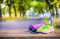 Pair of yellow green sport shoes towel water smart pone and headphones on wooden board. In the background forest or park trail. Royalty Free Stock Photo