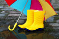 Pair of yellow rubber boots with an open umbrella Royalty Free Stock Photos