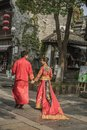 A pair of young couples who are facing each other wearing Chinese traditional red wedding dresses and smiling at each other in the