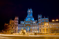 Palacio de comunicaciones and the cibeles fountain on plaza de cibeles illuminated at night in the city of madrid spain Royalty Free Stock Image