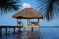 Palapa hut with thatched roof over caribbean sea overwater made of dried palm leaves Stock Photos