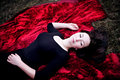 Pale woman in black dress lying on red carpet Royalty Free Stock Photography