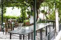 Paleokastritsa, Cofru, Greece- MAY 10, 2018 Inside looks of Taverna the greek restaurant with tables and chairs with the garden. r Royalty Free Stock Photo